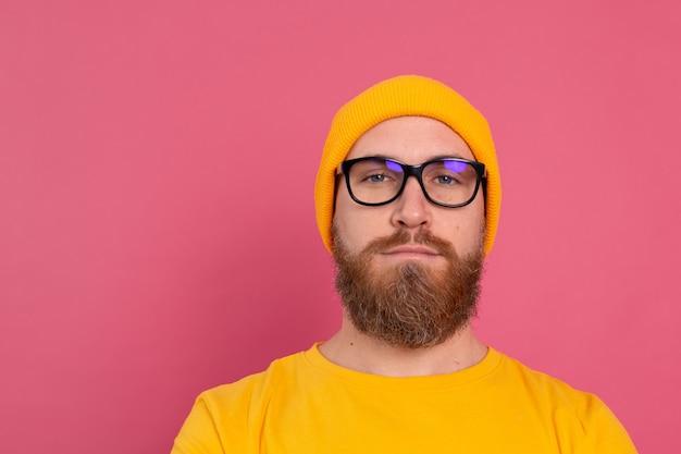 캐주얼 노란색 셔츠 모자와 분홍색 안경에 세련된 잘 생긴 유럽 수염 난된 남자의 초상화 무료 사진