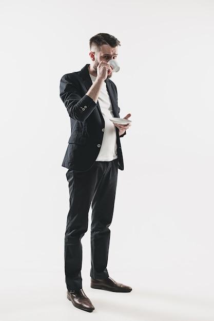 Портрет стильного красивого молодого человека, стоящего в студии. Бесплатные Фотографии