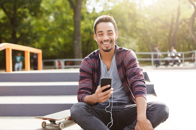 スタイリッシュな流行に敏感な男の肖像画は気楽な屋外の階段に座っている感じ、スケートボードに乗って長いトレーニングの後にかかっています、 無料写真