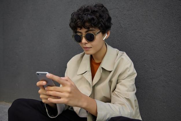 콘크리트 검은 벽 위에 포즈를 취하고 손에 스마트 폰을 유지하고 차분한 얼굴로 화면을 보면서 선글라스와 이어폰을 착용하는 곱슬 짧은 머리를 가진 세련된 예쁜 갈색 머리 여성의 초상화 무료 사진