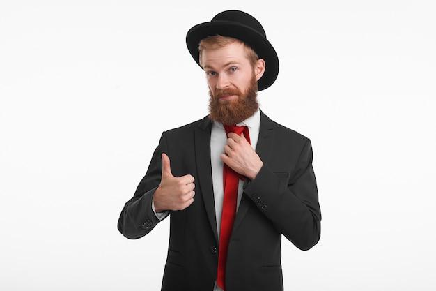 ファッショナブルなエレガントな服を着てポーズをとって、承認のサインとして親指を示し、このスーツと帽子を購入しようとしているトリミングされた長いひげを持つスタイリッシュな赤毛の若い男の肖像画 無料写真