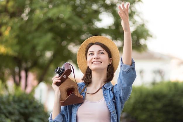 帽子とカメラを持つスタイリッシュな女性の肖像画 無料写真