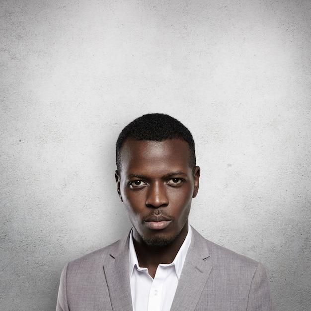 壁に立っている灰色のフォーマルなスーツを着て成功した自信を持って黒肌の起業家の肖像画 無料写真