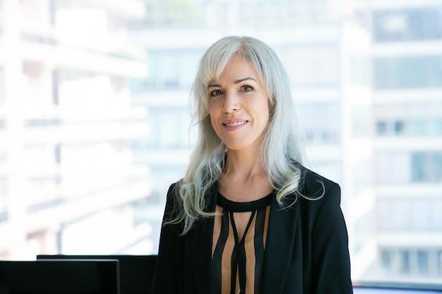 성공적인 회색 머리 여성 Ceo의 초상화와 미소. 콘텐츠는 사무실 방에서 포즈를 취하는 아름다운 사업가를 경험했습니다. 비즈니스, 회사, 외모 및 표현 개념 무료 사진