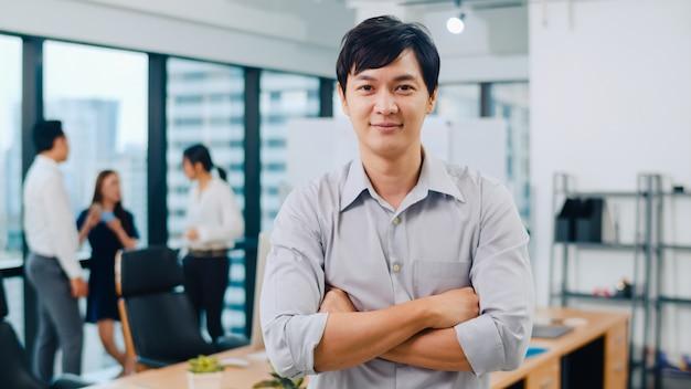성공적인 잘 생긴 임원 사업가 스마트 캐주얼 카메라를보고 웃 고, 무기 현대 사무실 직장에서 넘어의 초상화. 현대 회의실에 서있는 젊은 아시아 사람. 무료 사진