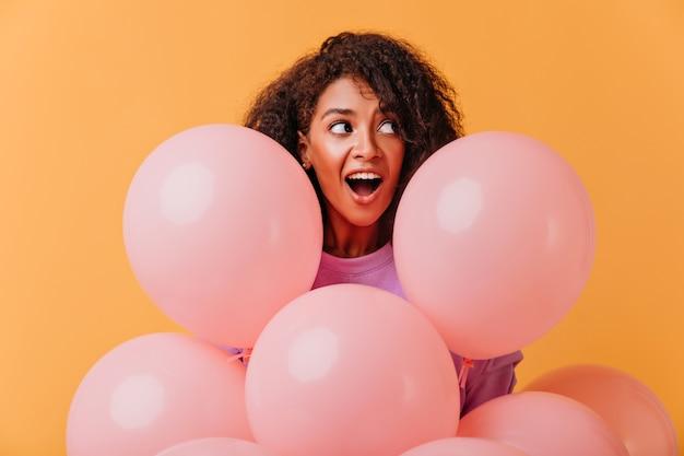 풍선과 함께 포즈를 취하는 동안 멀리보고 놀란 된 생일 소녀의 초상화. 재미있는 아프리카 아가씨 파티 동안 장난. 무료 사진