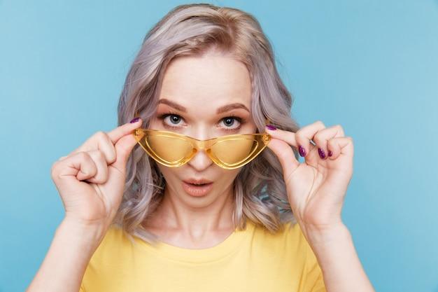 カメラのポーズと青い壁に立っている黄色いメガネを持って驚いたかわいい女の子の肖像画 Premium写真