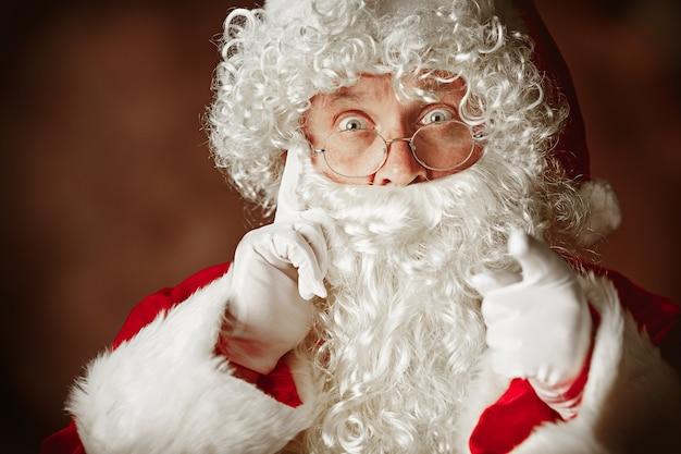 고급스러운 흰 수염, 산타의 모자와 빨간색에서 빨간색 의상으로 산타 클로스 의상에서 놀란 남자의 초상화 무료 사진