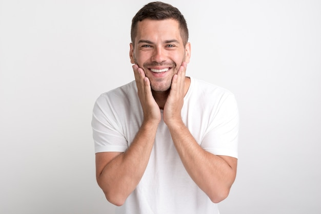 無地の背景に立っている白いtシャツに驚いた男の肖像 Premium写真
