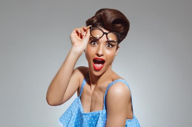 Портрет удивленной женщины в стиле пин-ап в очках Бесплатные Фотографии