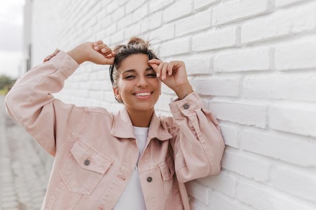 흰색 건물에 대해 포즈를 취하는 가벼운 데님 재킷에 검게 그을린 젊은 갈색 머리 여자의 초상화 무료 사진
