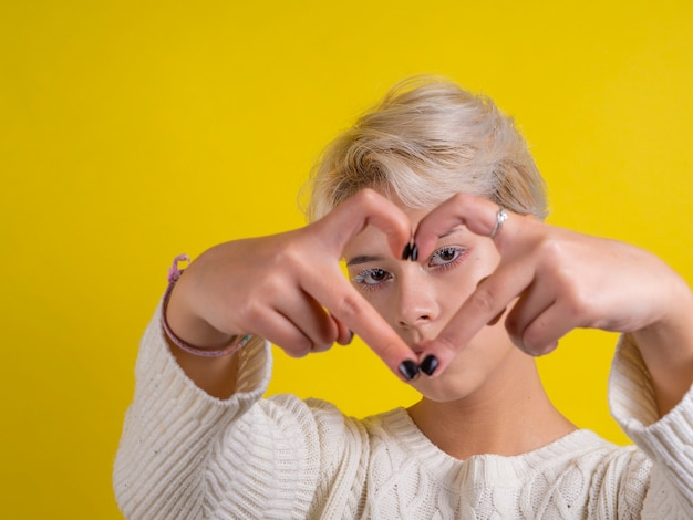 彼女の手でハートの形を作る十代の少女の肖像画 Premium写真