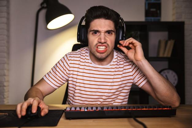 Портрет напряженного молодого человека 20 лет в гарнитуре, кричащего, сидя за столом с компьютером в комнате и смотрящего на монитор Premium Фотографии