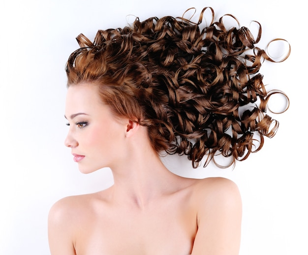 바닥에 누워 아름다움 긴 곱슬 머리를 가진 아름 다운 젊은 여자의 초상화 무료 사진