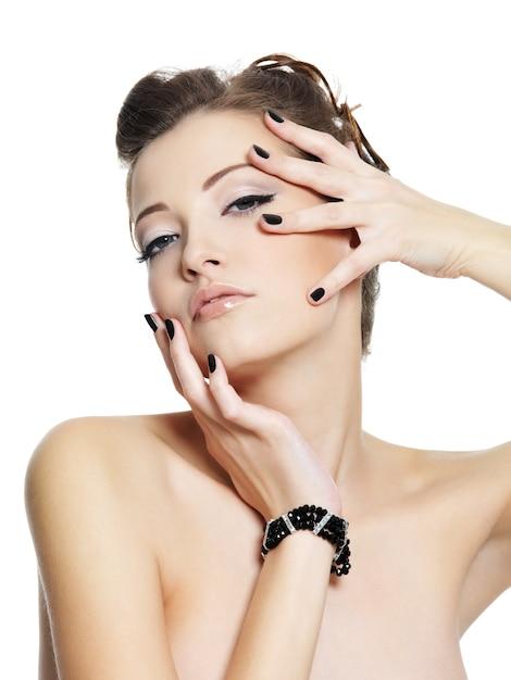 Портрет гламурной молодой женщины с черными ногтями, позирующей на белом Бесплатные Фотографии