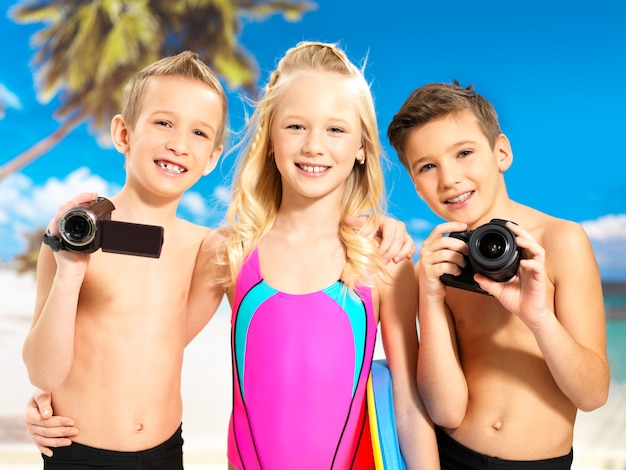 ビーチで楽しんでいる幸せな子供たちの肖像画。写真とビデオカメラを手に立っている小学生の子供たち。 無料写真