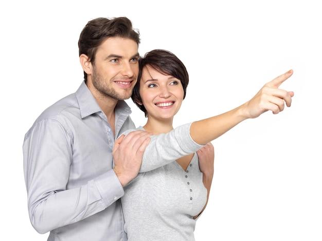 遠くを見て、指している幸せなカップルの肖像画、。 無料写真
