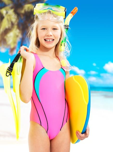 ビーチで楽しんでいる幸せな女の子の肖像画。小学生の女の子は頭に水泳マスクを付けた明るい色の水着で立っています。 無料写真