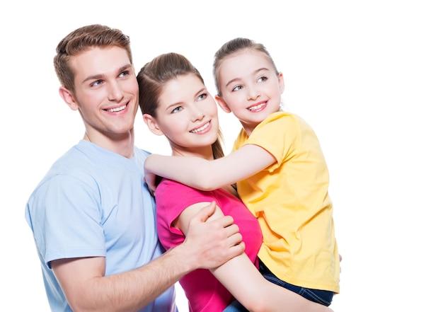Портрет счастливой молодой семьи с ребенком в разноцветных рубашках - изолированные на белой стене. Бесплатные Фотографии
