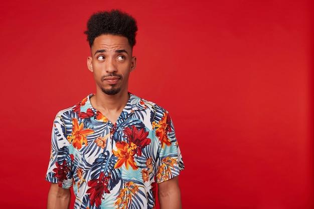 Портрет думающего молодого афро-американского парня, одетого в гавайскую рубашку, смотрящего прямо на copyspace, стоящего на красном фоне. Бесплатные Фотографии