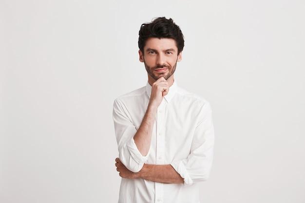 Портрет вдумчивого привлекательного молодого бизнесмена с щетиной в рубашке выглядит задумчивым и уверенным, изолированным на белом держит руки сложенными Бесплатные Фотографии