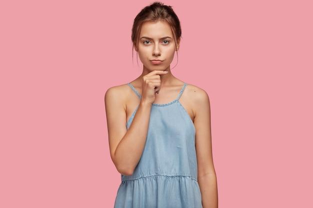 Портрет задумчивой серьезной девушки держит подбородок, смотрит с расстроенным выражением лица прямо в камеру Бесплатные Фотографии