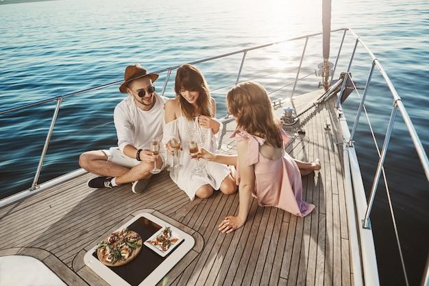 ヨットのボードに座って、シャンパンを飲んで元気に話している間ディナーを楽しんでいる3人の魅力的なヨーロッパの人々の肖像画。友達は一年中頑張って太陽と海を楽しみました 無料写真
