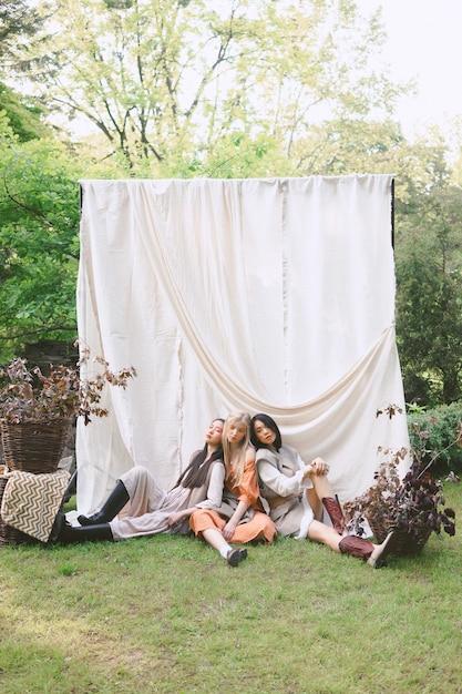 昼間に地面に座って、庭で3人の美しい女性の肖像画。 無料写真