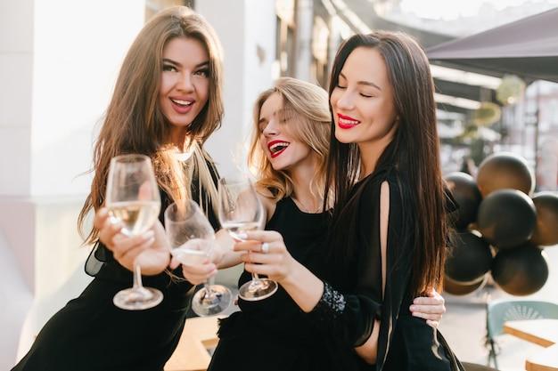 シャンパンで重要なイベントを祝う黒い服を着た3人の姉妹の肖像画 無料写真