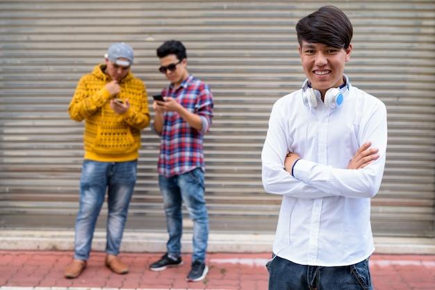 방콕, 태국의 거리에서 창고 문에 서있는 세 젊은 아시아 남자의 초상 프리미엄 사진