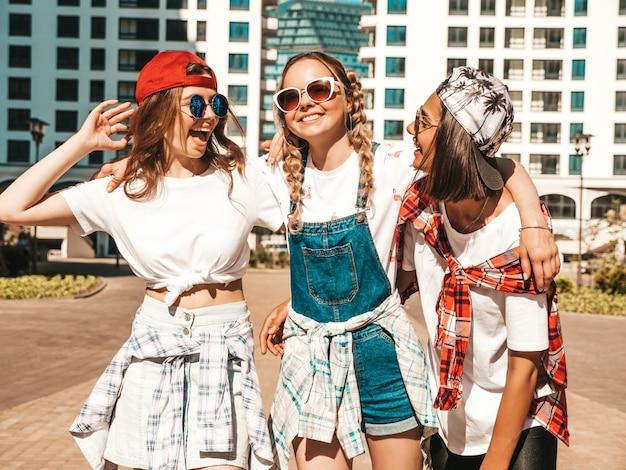 トレンディな夏服の3人の若い美しい笑顔の流行に敏感な女の子の肖像画。通りの背景にポーズの屈託のない女性。楽しさとクレイジーになる肯定的なモデル 無料写真