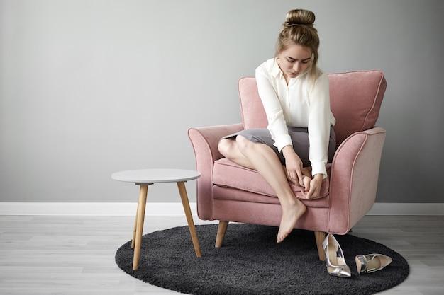 一日中ハイヒールを履いているために痛みを和らげるために肘掛け椅子に座って足をマッサージしているフォーマルな服装で疲れ果てた若い女性サラリーマンの肖像画。健康とウェルネス 無料写真