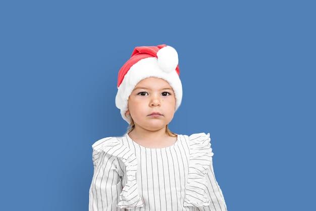 クリスマスに赤い帽子の幼児の女の子の肖像画。 Premium写真