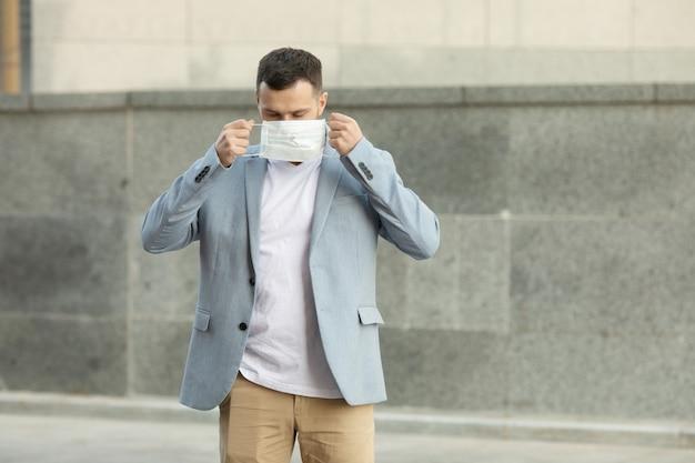 Портрет модного мужчины в защитной маске, гуляющего по городу Premium Фотографии