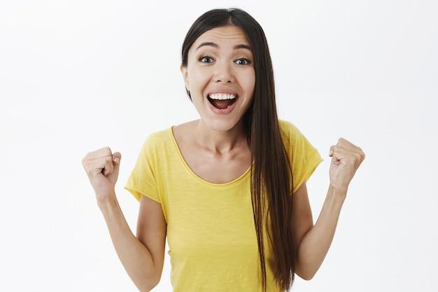 Портрет торжествующей радостной и красивой девушки в желтой футболке, поднимающей сжатые кулаки, изумленный и удивленный победой Бесплатные Фотографии