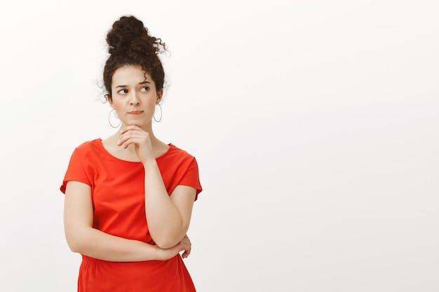 Портрет обеспокоенной напряженной привлекательной студентки в стильном повседневном красном платье, скрещивающей одну руку на груди и держащей ладонь на подбородке Бесплатные Фотографии
