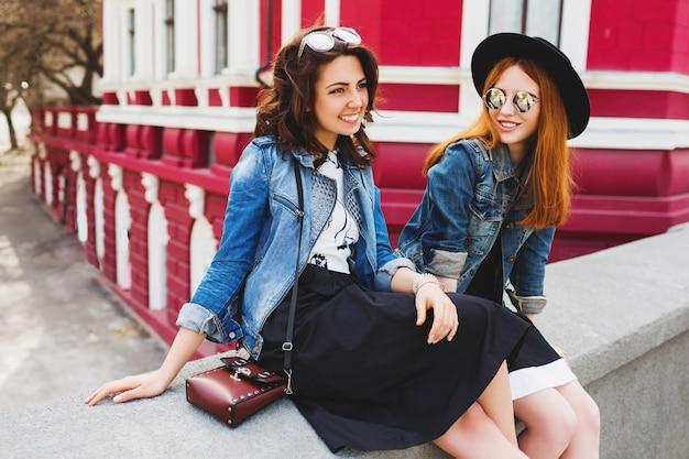 笑って、市内中心部の通りに屋外で話している2人の親友の肖像画 無料写真