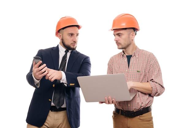 白い孤立した背景の上に立って、ラップトップのディスプレイを見ている保護オレンジ色のヘルメットの2人のビルダーの肖像画。建設プロジェクトについて話し合う Premium写真