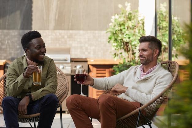 屋外テラスのラウンジチェアでリラックスしながらワインを楽しむ2人の現代的な男性の肖像画、 Premium写真