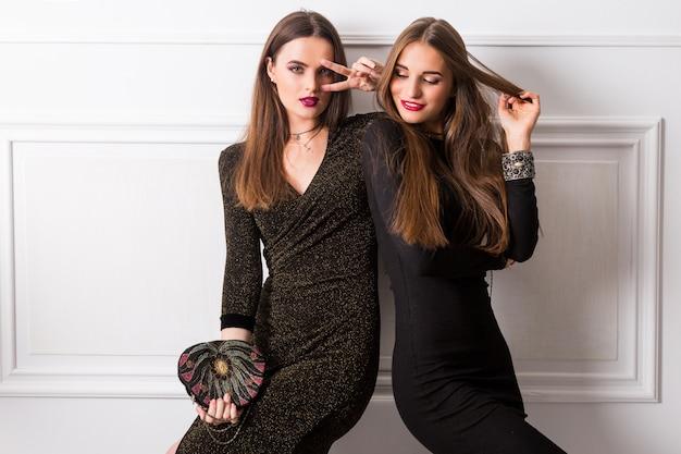 白い壁でポーズグラマーロングドレスで2つのエレガントな若い女性の肖像画 無料写真