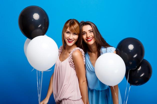 파란색 벽을 통해 파티에서 쉬고 두 여자의 초상화 무료 사진