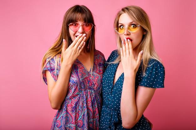 ピンクの壁で楽しい2人の陽気な親友の女性の肖像画。明るい印刷されたヴィンテージの夏のドレスとサングラスを着用し、一緒におしゃべりをして、感情を退出しました。 無料写真