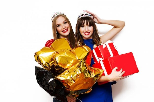 Портрет двух красивых женщин с яркими воздушными шарами и подарочными коробками Бесплатные Фотографии