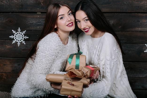 Портрет двух хорошеньких молодых женщин с рождественскими подарками Бесплатные Фотографии