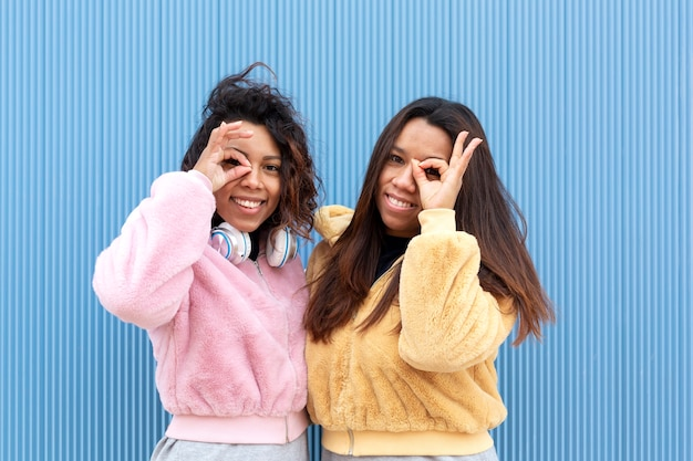 좋아의 상징을 형성하는 그들의 얼굴 가까이에 그들의 손가락을 넣어 두 웃는 친구의 초상화. 그들은 파란색 배경에 있습니다. 텍스트를위한 공간. 프리미엄 사진