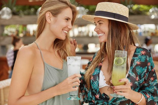 Портрет двух женщин встречаются в столовой на открытом воздухе, чокаются с холодными коктейлями, смотрят друг на друга с положительными эмоциями. довольно раскованные самки расслабляются во время вечеринки, веселятся вместе Бесплатные Фотографии
