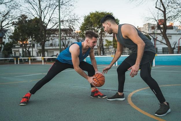 Портрет двух молодых друзей, играющих в баскетбол и весело проводящих время на площадке на открытом воздухе. спортивная концепция. Бесплатные Фотографии