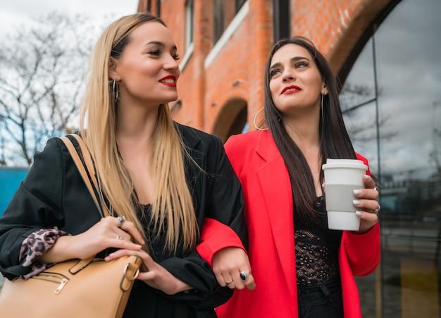 Портрет двух молодых друзей, хорошо проводящих время вместе во время прогулки на свежем воздухе по улице. концепции образа жизни и дружбы. Premium Фотографии