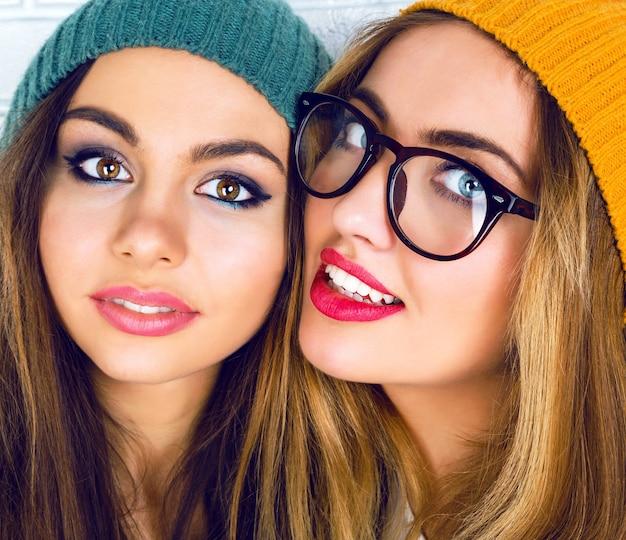 明るいメイク、帽子、メガネを身に着けている2人の若いかわいい女の子の肖像画 無料写真