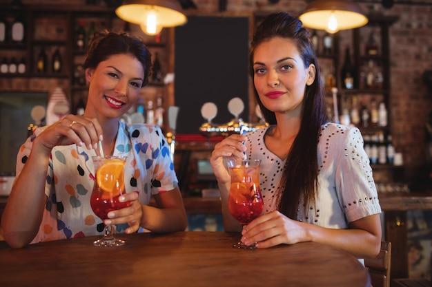 Портрет двух молодых женщин, имеющих коктейльные напитки Premium Фотографии